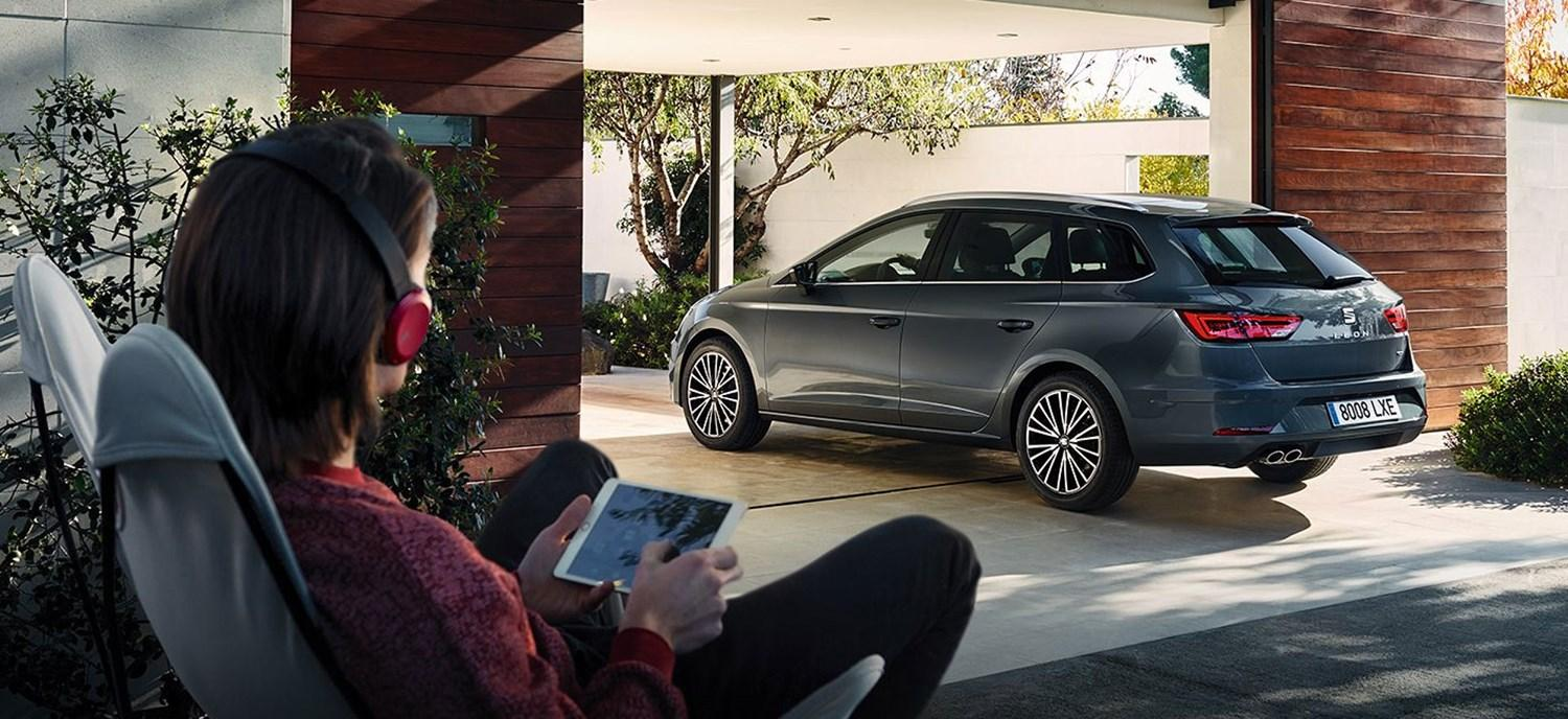 Woman with tablet and headphones looking at SEAT Leon Estate