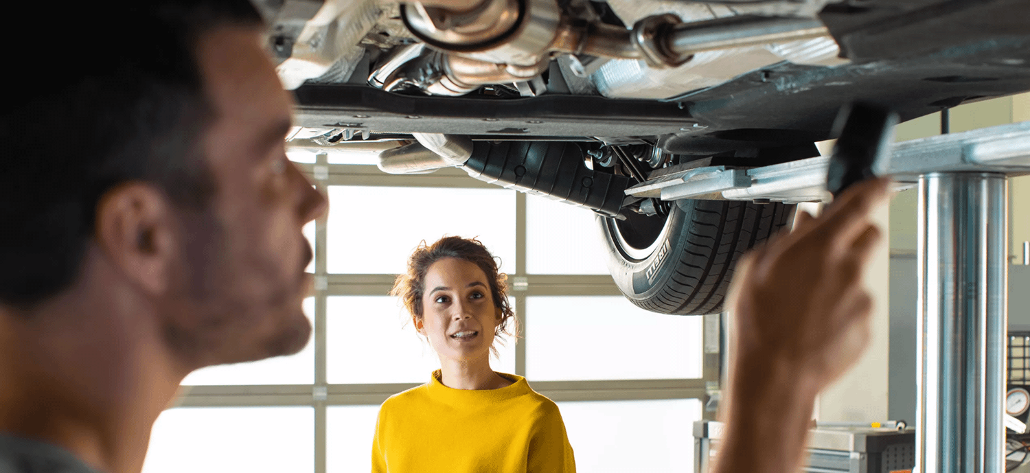Man investigating underside of a car while a lady watches on