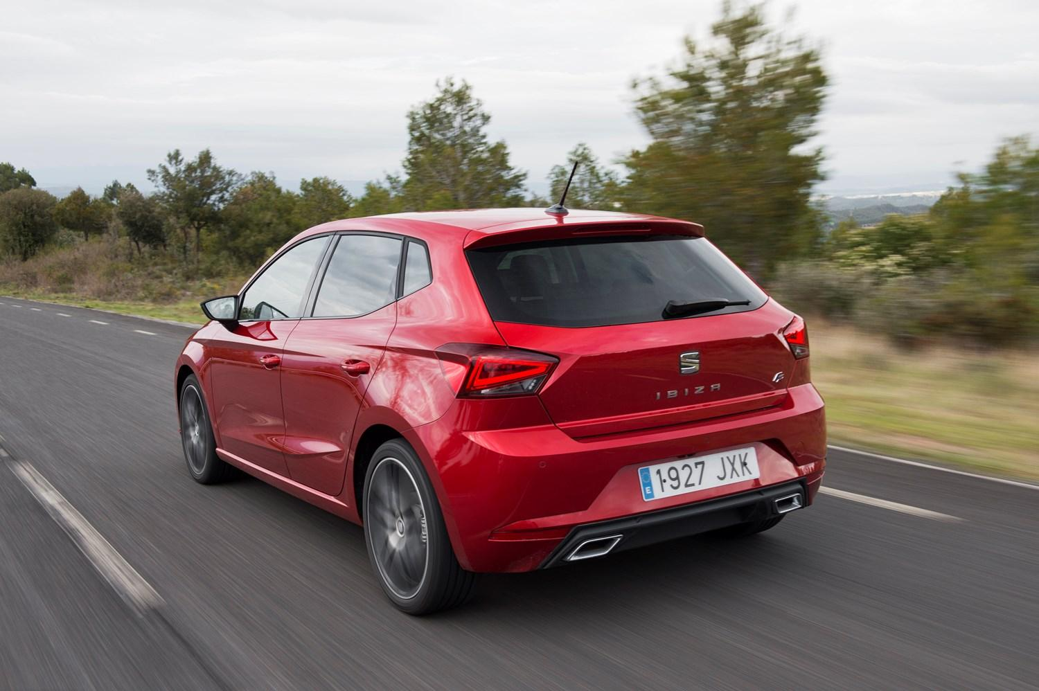 Red SEAT Ibiza on road from behind