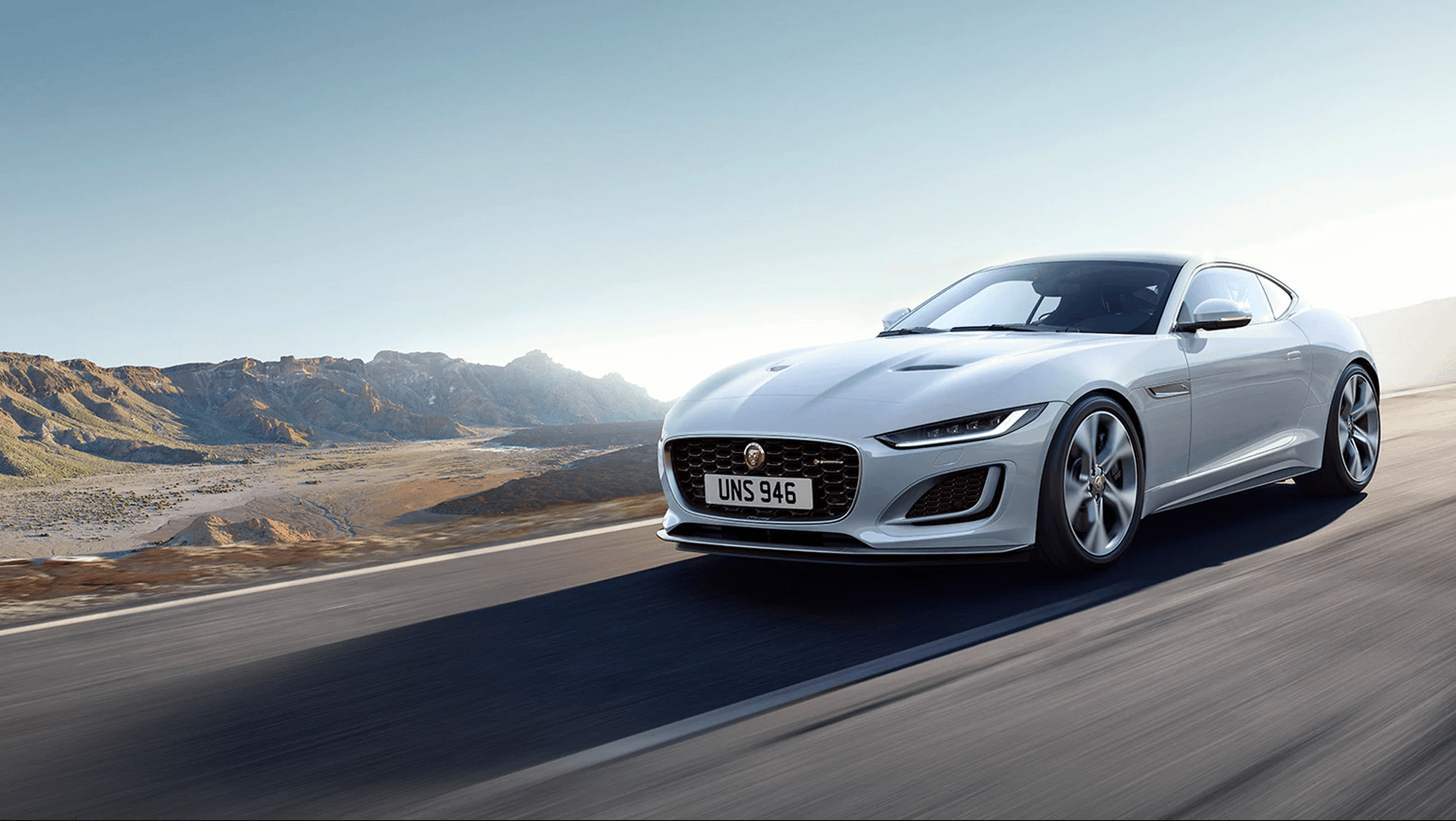 Silver Jaguar F-Type with mountainous backdrop