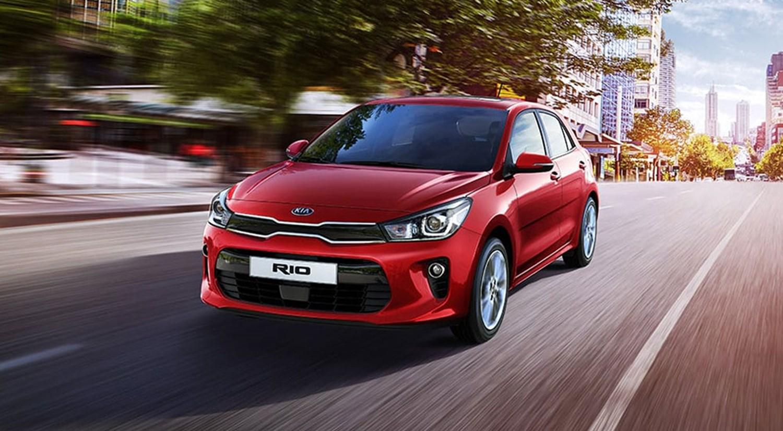 Red Kia Rio driving on road