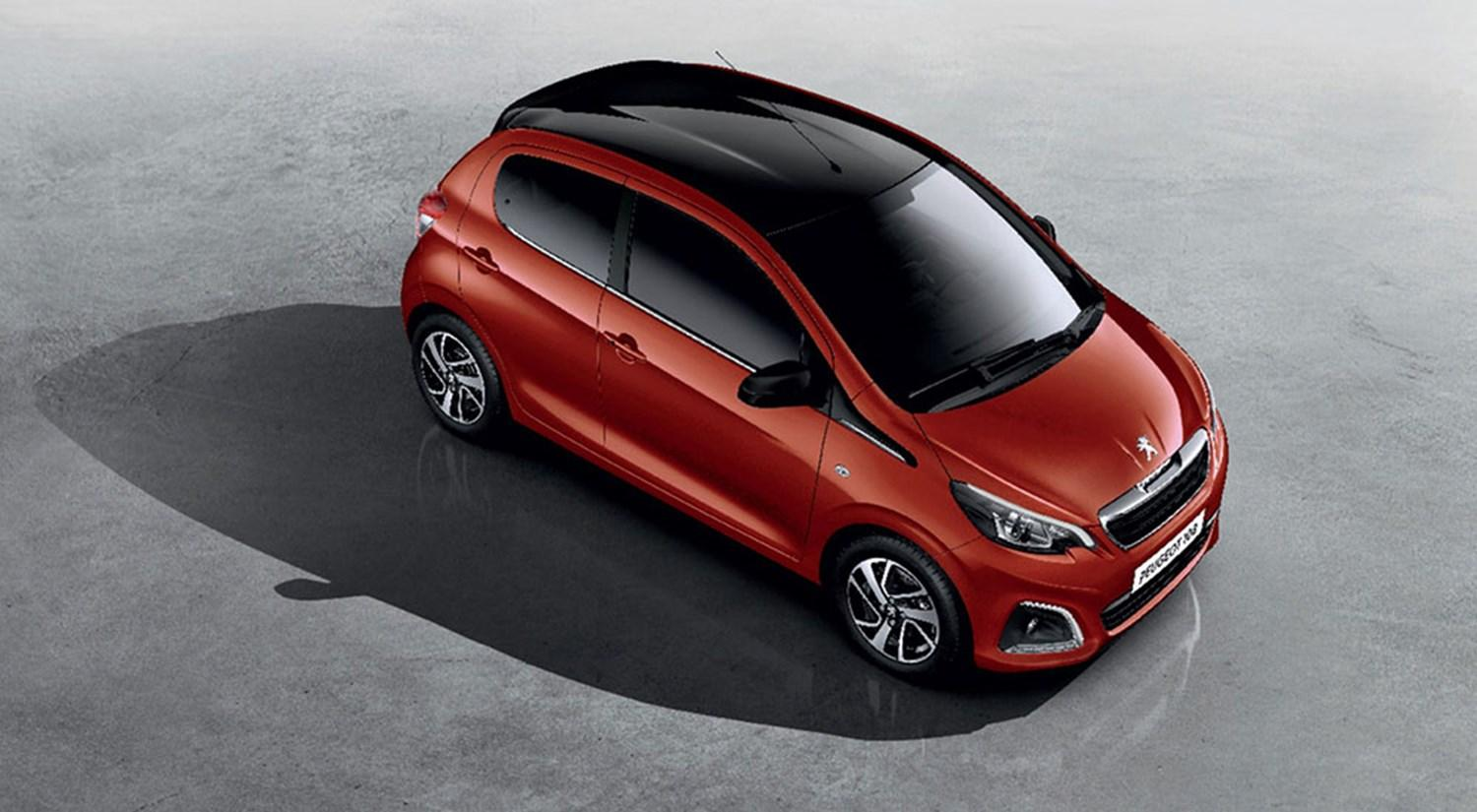 Red Peugeot 108 with black roof parked in studio