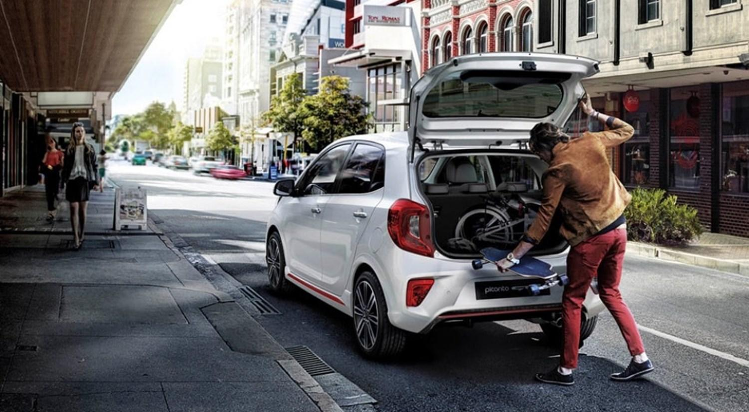 White Kia Picanto parked on street with boot open