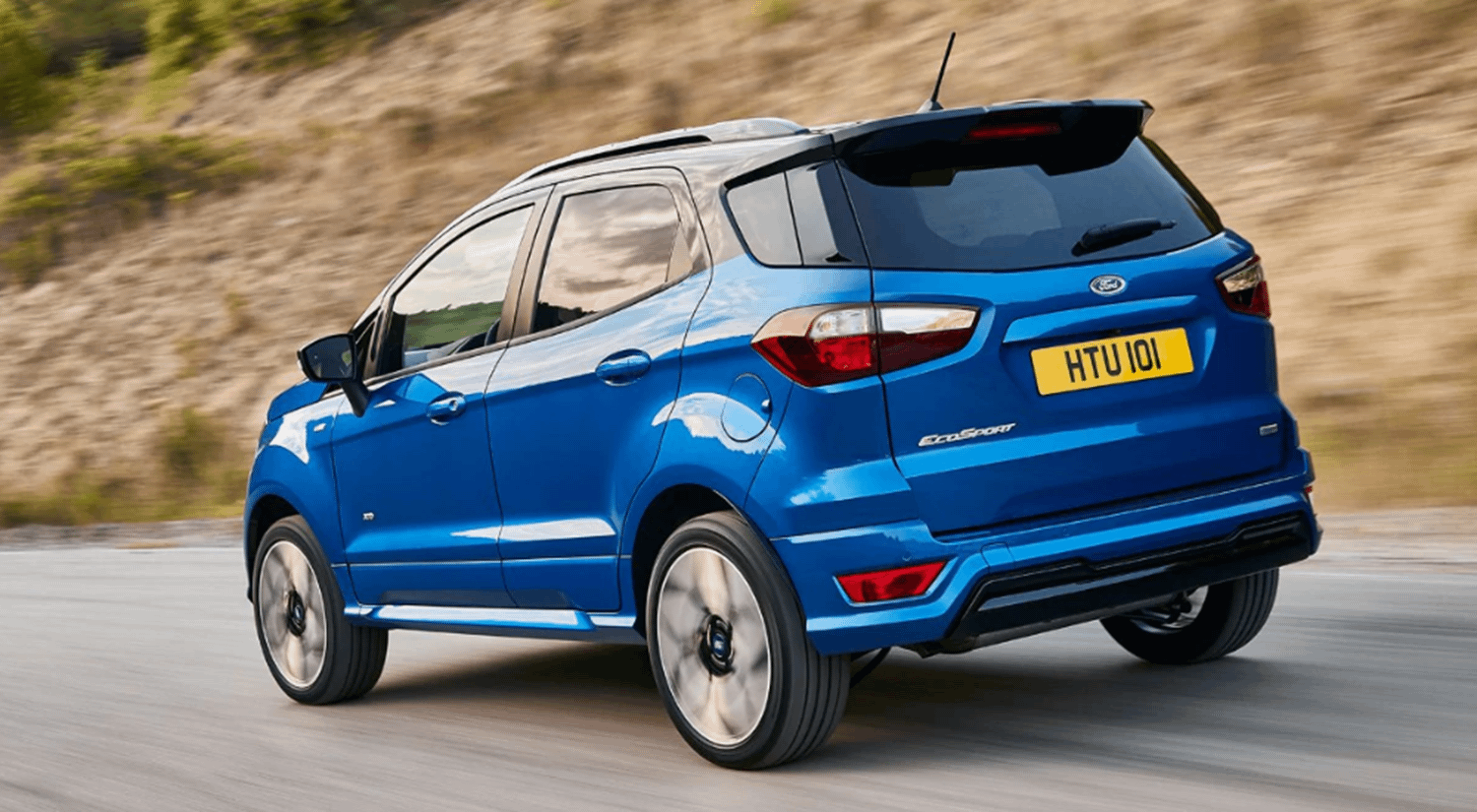 Rear view blue Ford EcoSport driving on road