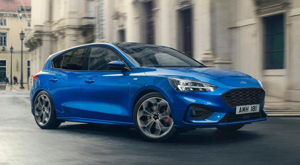 Blue Ford Focus driving down street