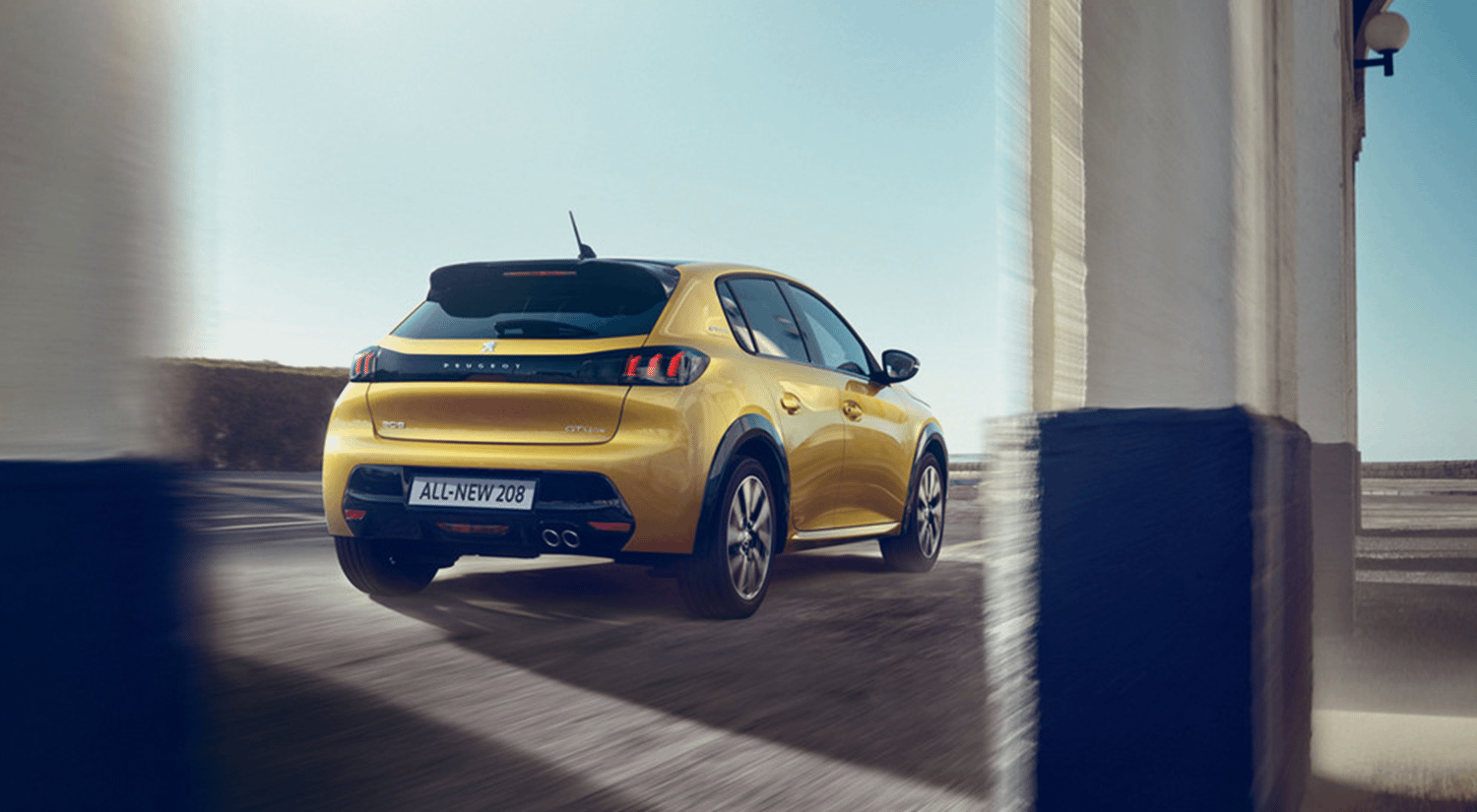 Rear view yellow All-New Peugeot 208 driving