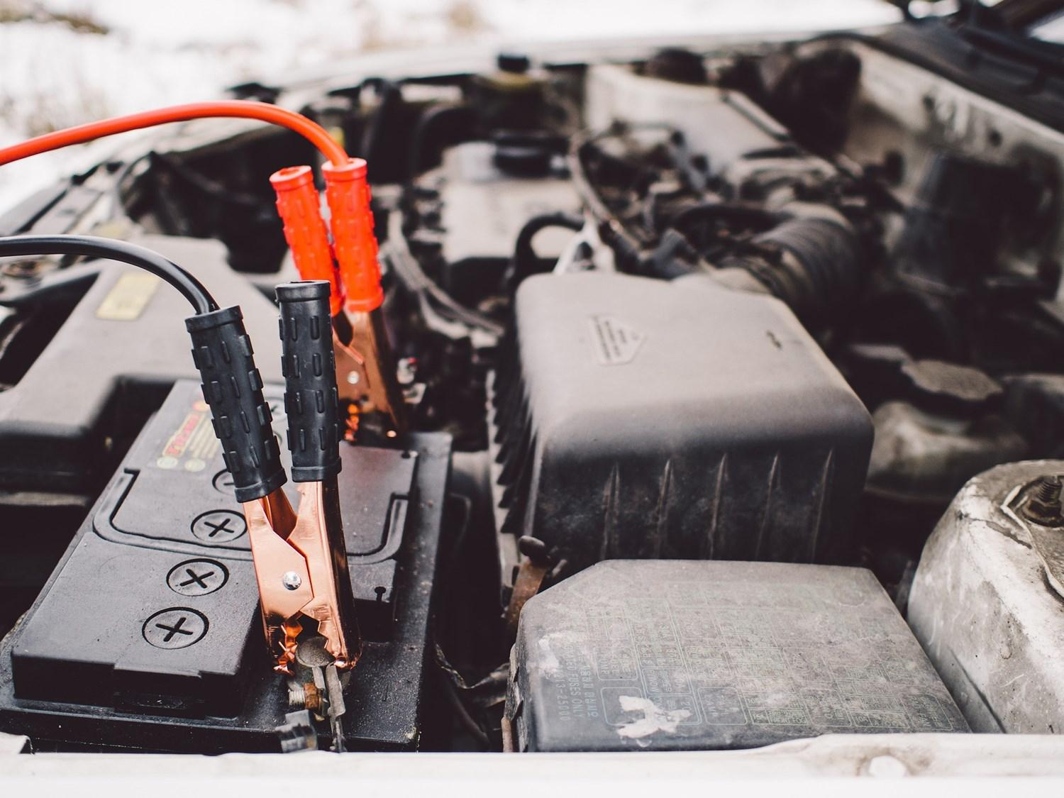 Close up of jump cables attached to car battery