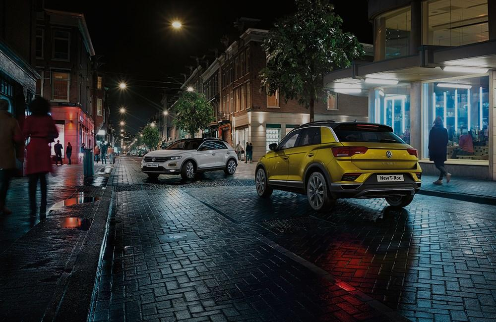 Yellow and white Volkswagen T-Roc in city street at night