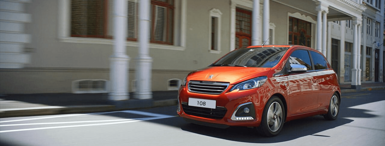 Orange Peugeot 108 driving along street