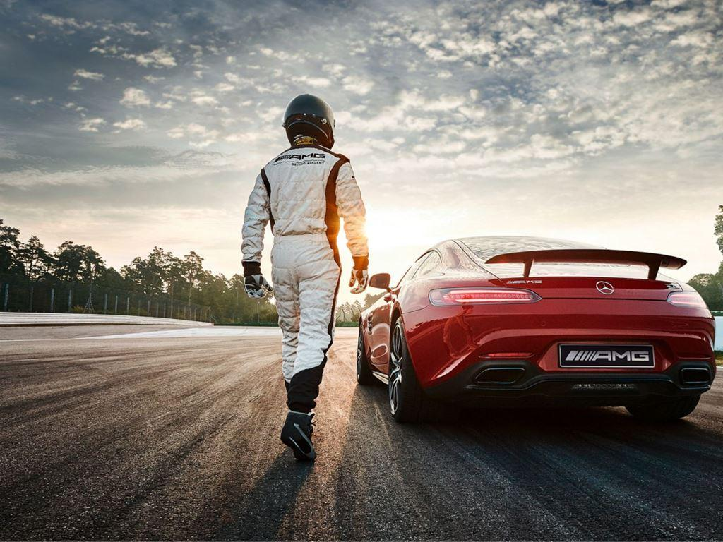 Racing driver next to red Mercedes-AMG GT 4-Door Coupe
