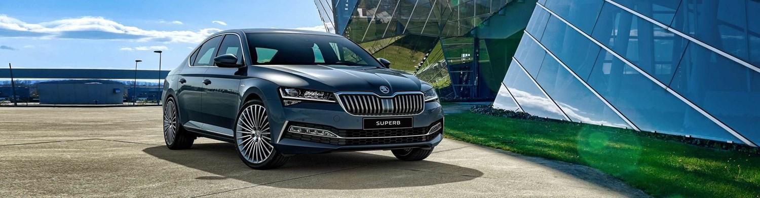 Skoda Superb in front of glass building
