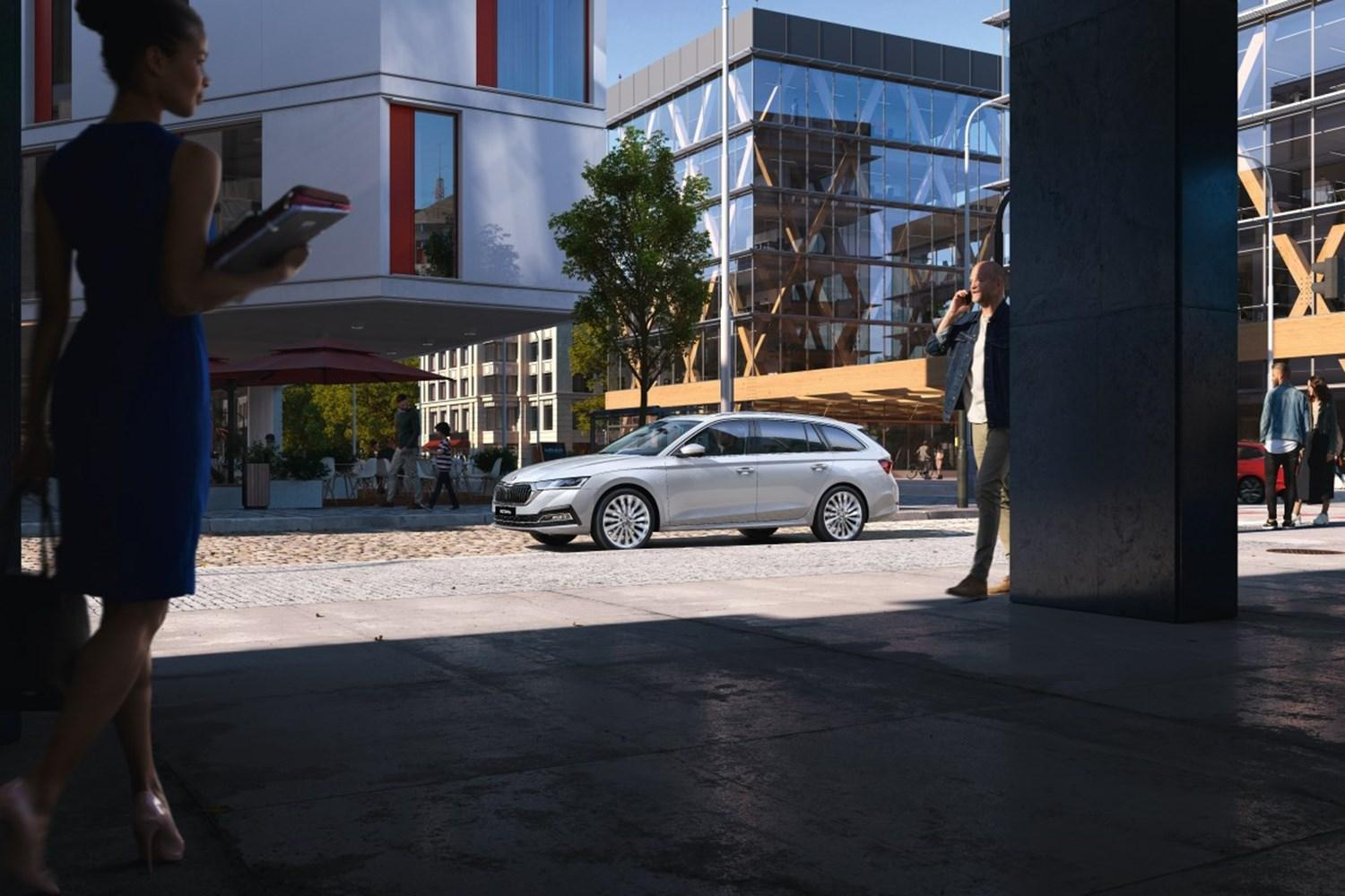 Silver Skoda Superb Estate among modern buildings