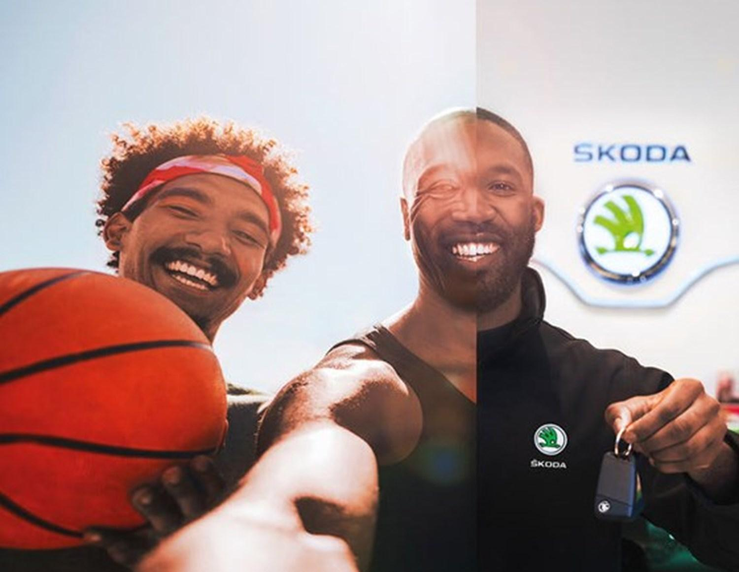 Man with basketball and man with set of car keys smiling in a Skoda showroom