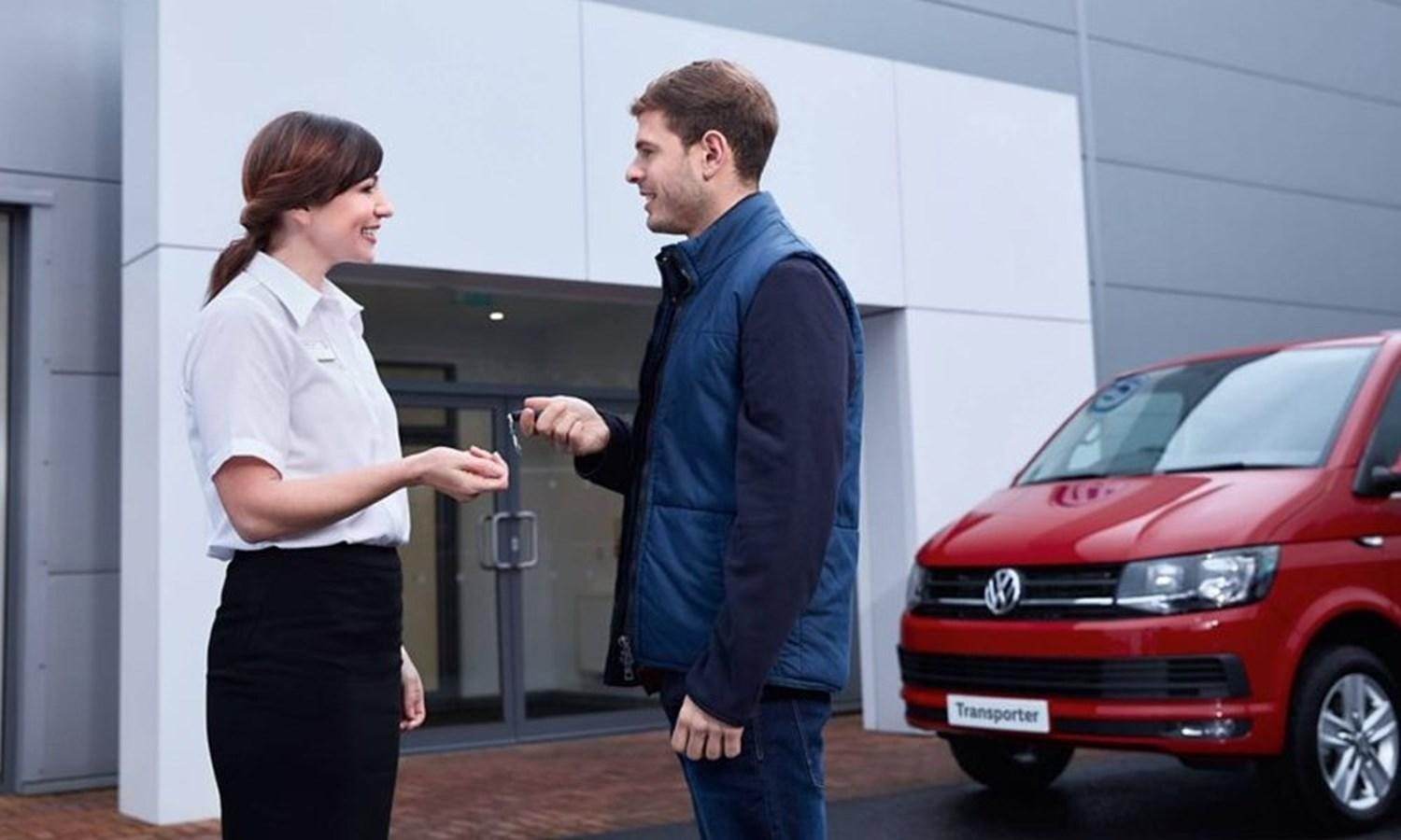 Man and woman exchanging car key in front of new red Volkswagen Transporter