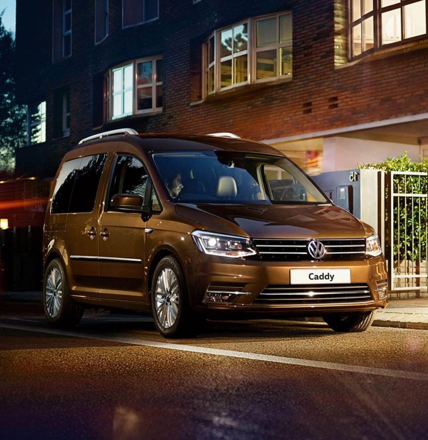 Brown Volkswagen Caddy parked on street at night