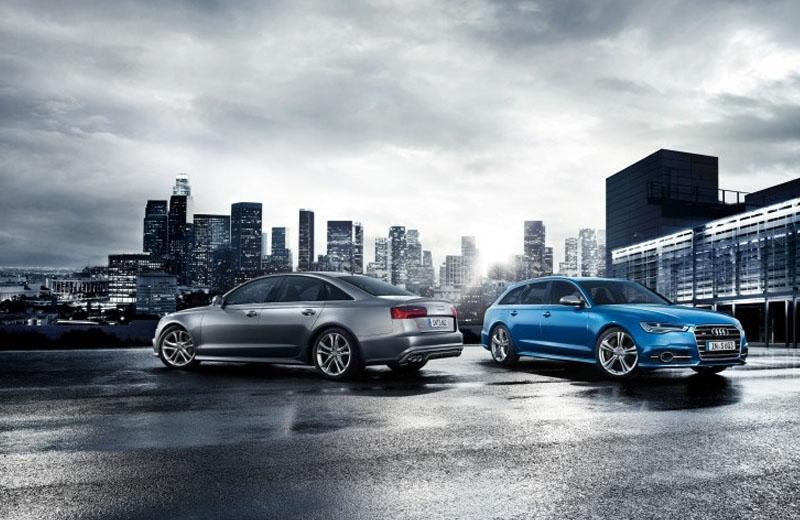 Grey Audi saloon and blue Audi Estate in front of cityscape