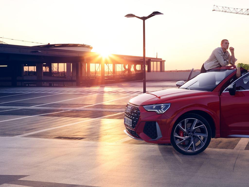 Red Parked RS Q3 with two people talking