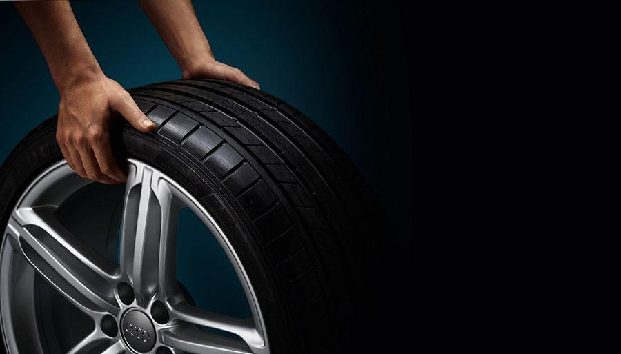 Audi tyre being held by two hands