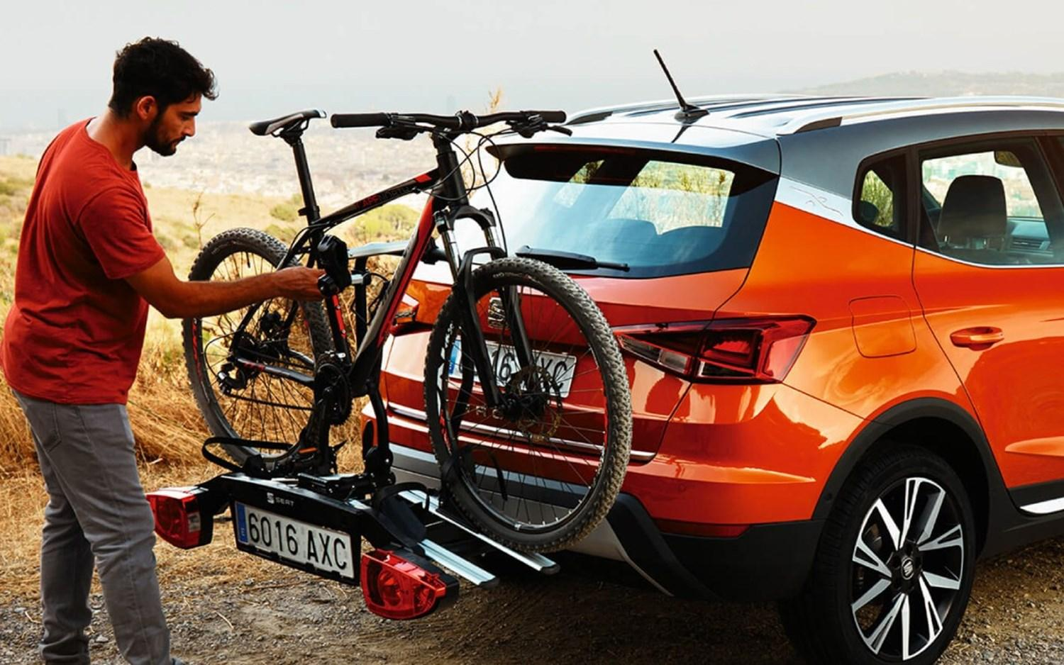 Man loading bike on to rear bike rack of red SEAT Arona