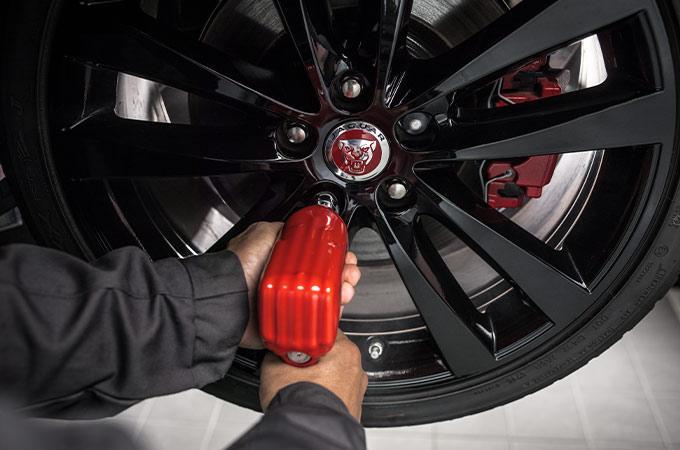 Mechanic working on Jaguar wheel