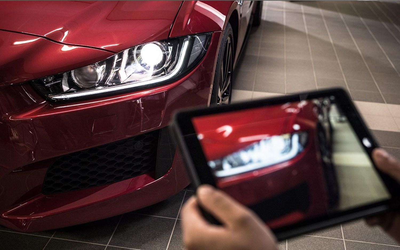 Front corner of red jaguar being photographed on a tablet