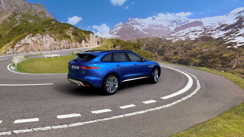 Blue Jaguar SUV driving down winding hills