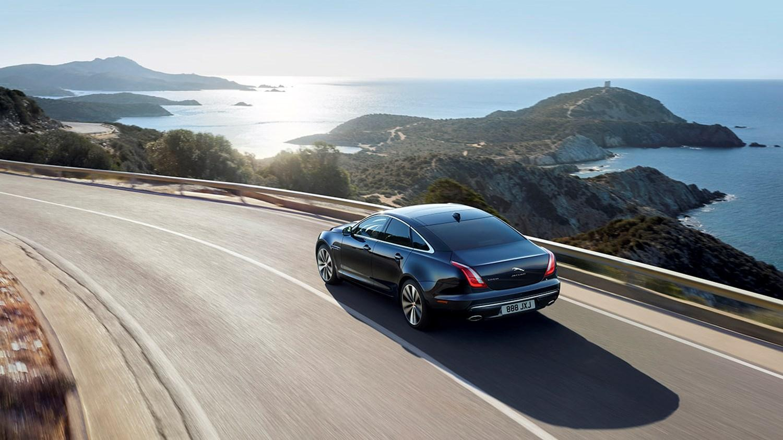 Jaguar Saloon driving roadside along the seafront
