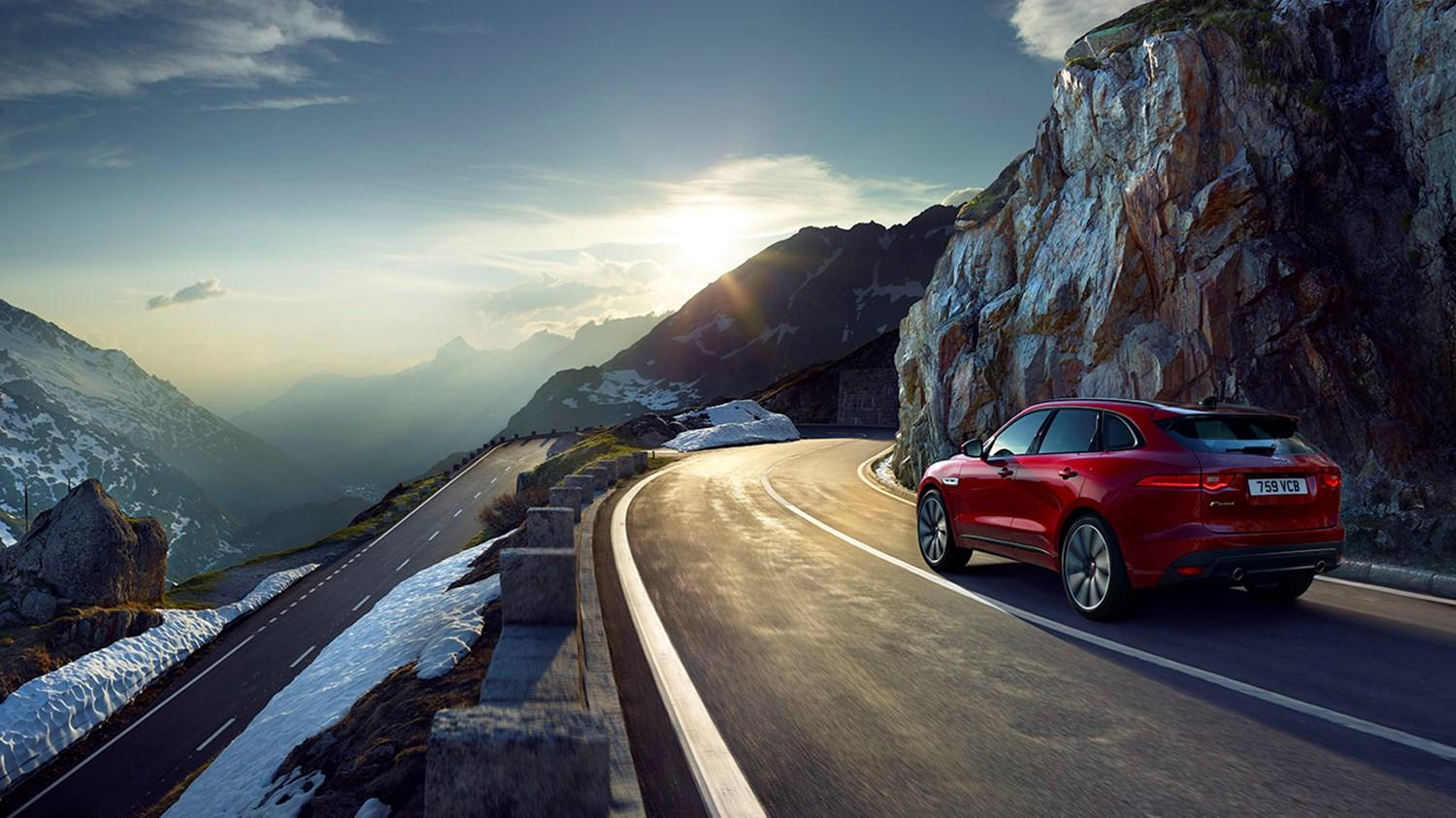 Red Jaguar E-Pace driving a mountain road