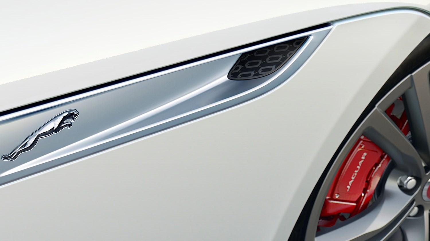 close up of Jaguar sill on a cream jaguar with red brake calipers