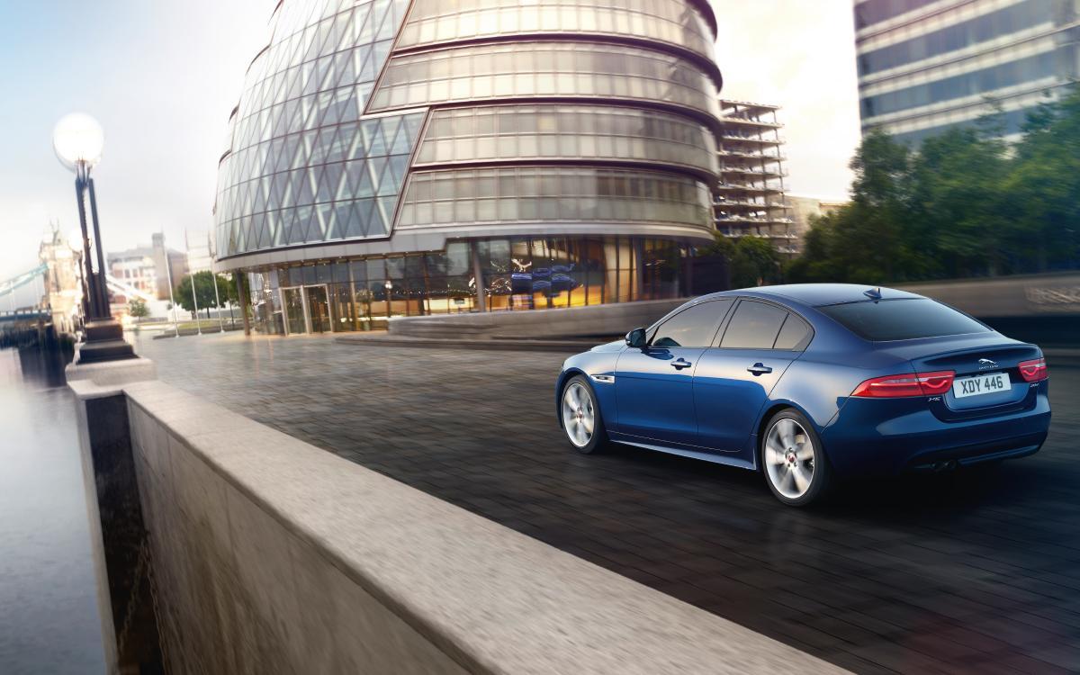 Blue Jaguar XE outside modern building