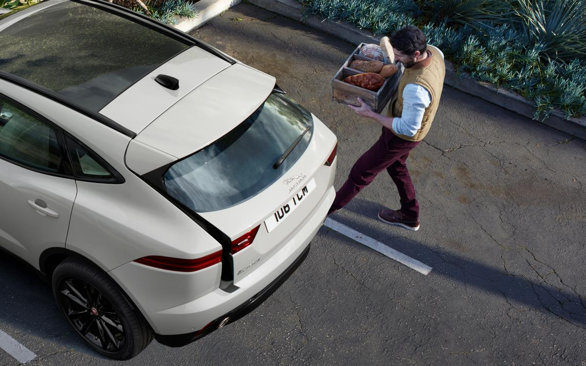 Man carrying box of vegetables to white Jaguar E-Pace