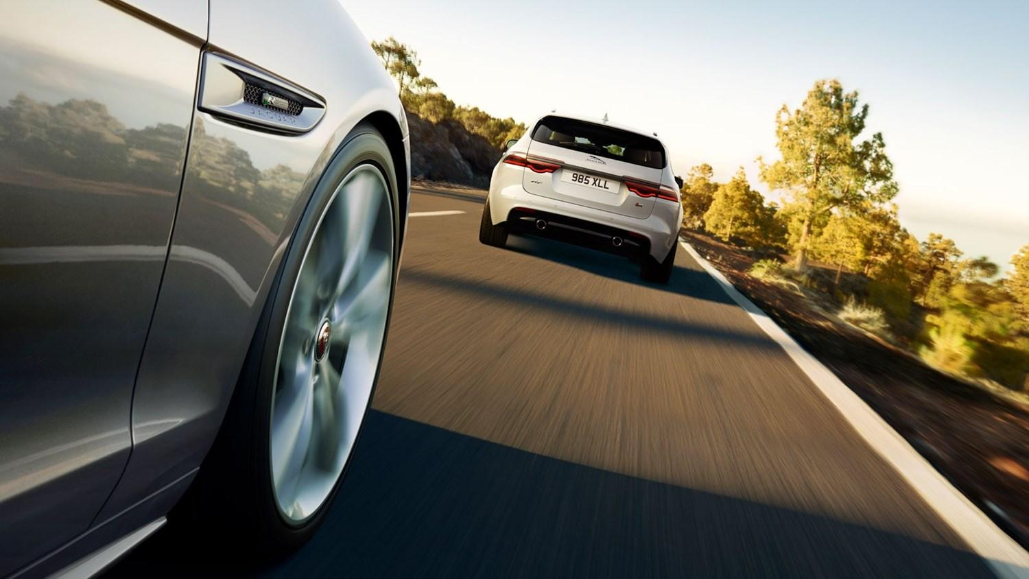 Rear view of white Jaguar XF estate from wheel arch of trailing Jaguar
