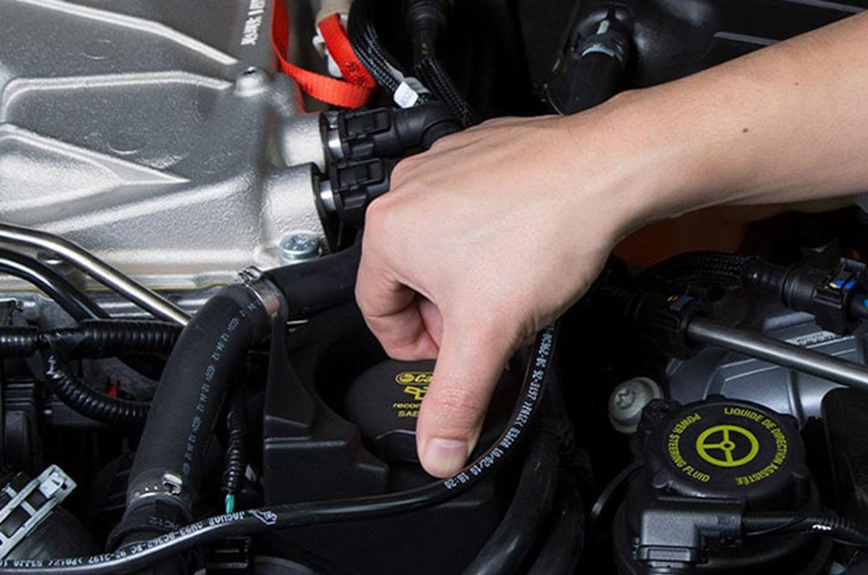Oil cap being opened in Jaguar engine