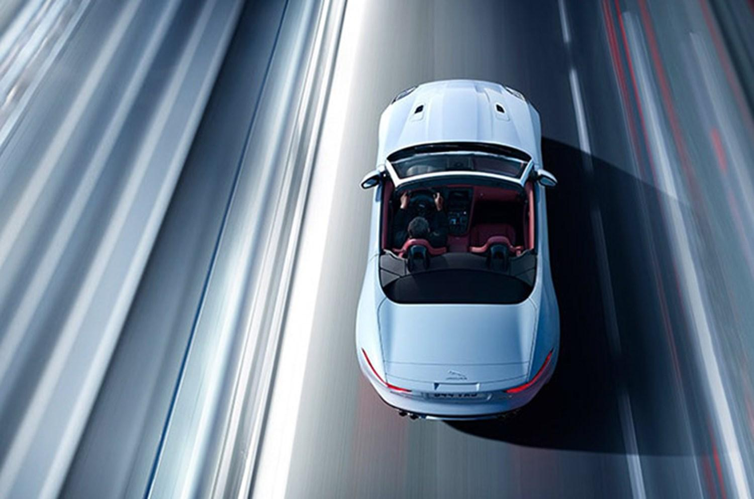 Arial view of white jaguar cabriolet driving