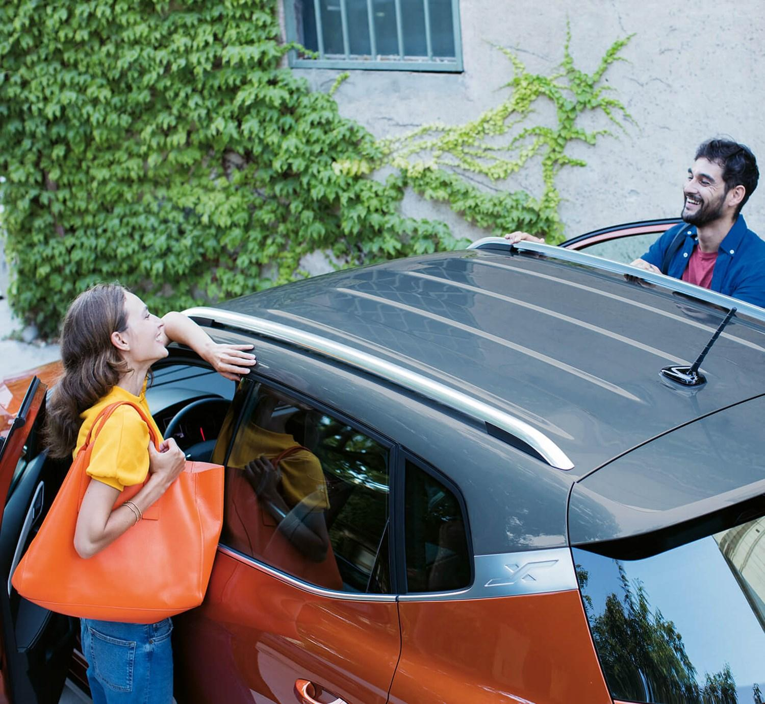 Couple smiling looking over an orange SEAT Arona