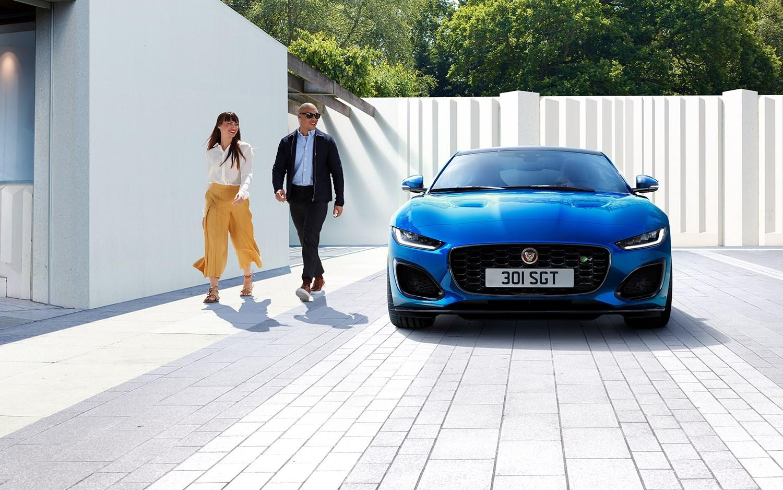 Man and woman walking past parked blue Jaguar