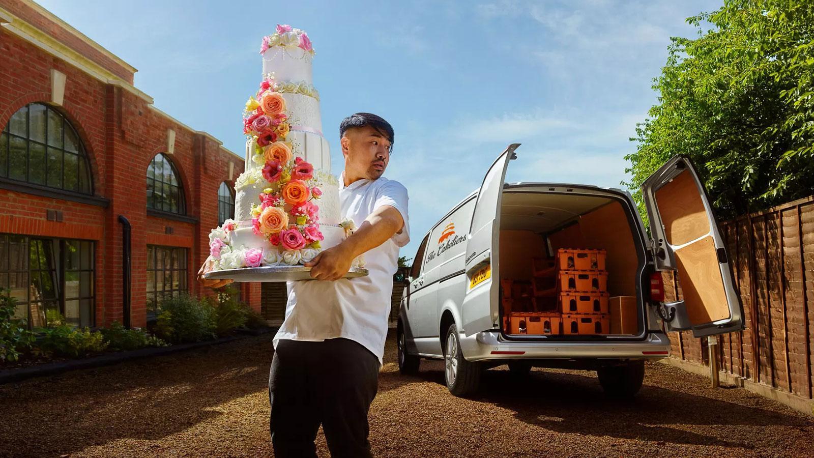 Man carrying wedding cake from Volkswagen van