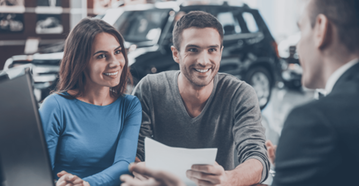 Couple smiling in a car showroom