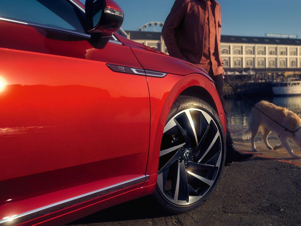 Person and Dog next to red Volkswagen Arteon Shooting Brake