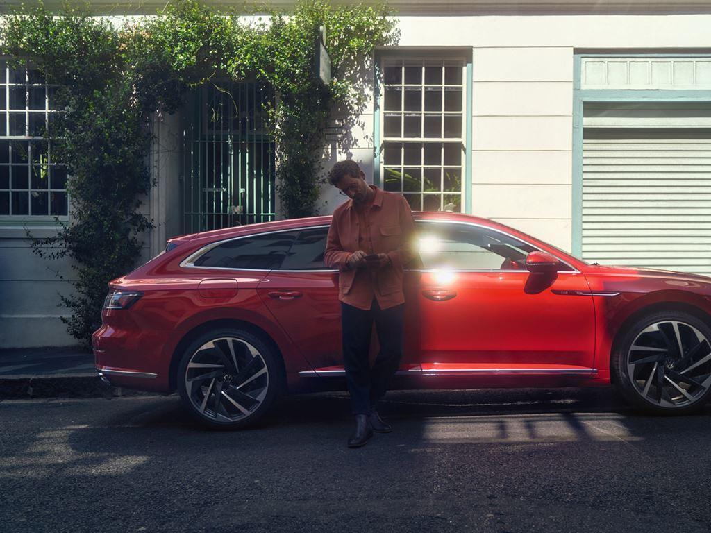 Man stood by parked Volkswagen Arteon Shooting Brake