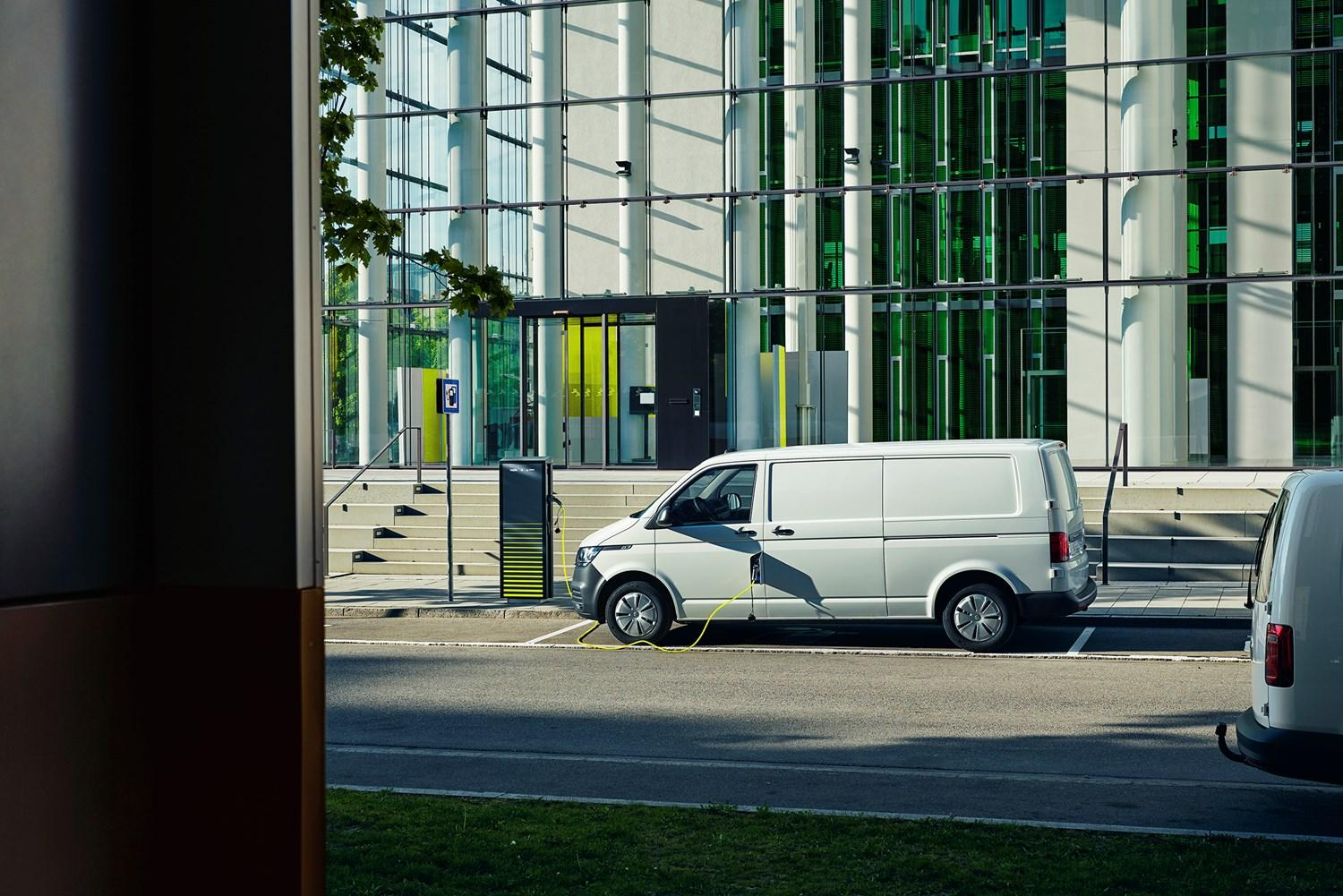 ABT e-transporter plugged into roadside charging point in front of glass building