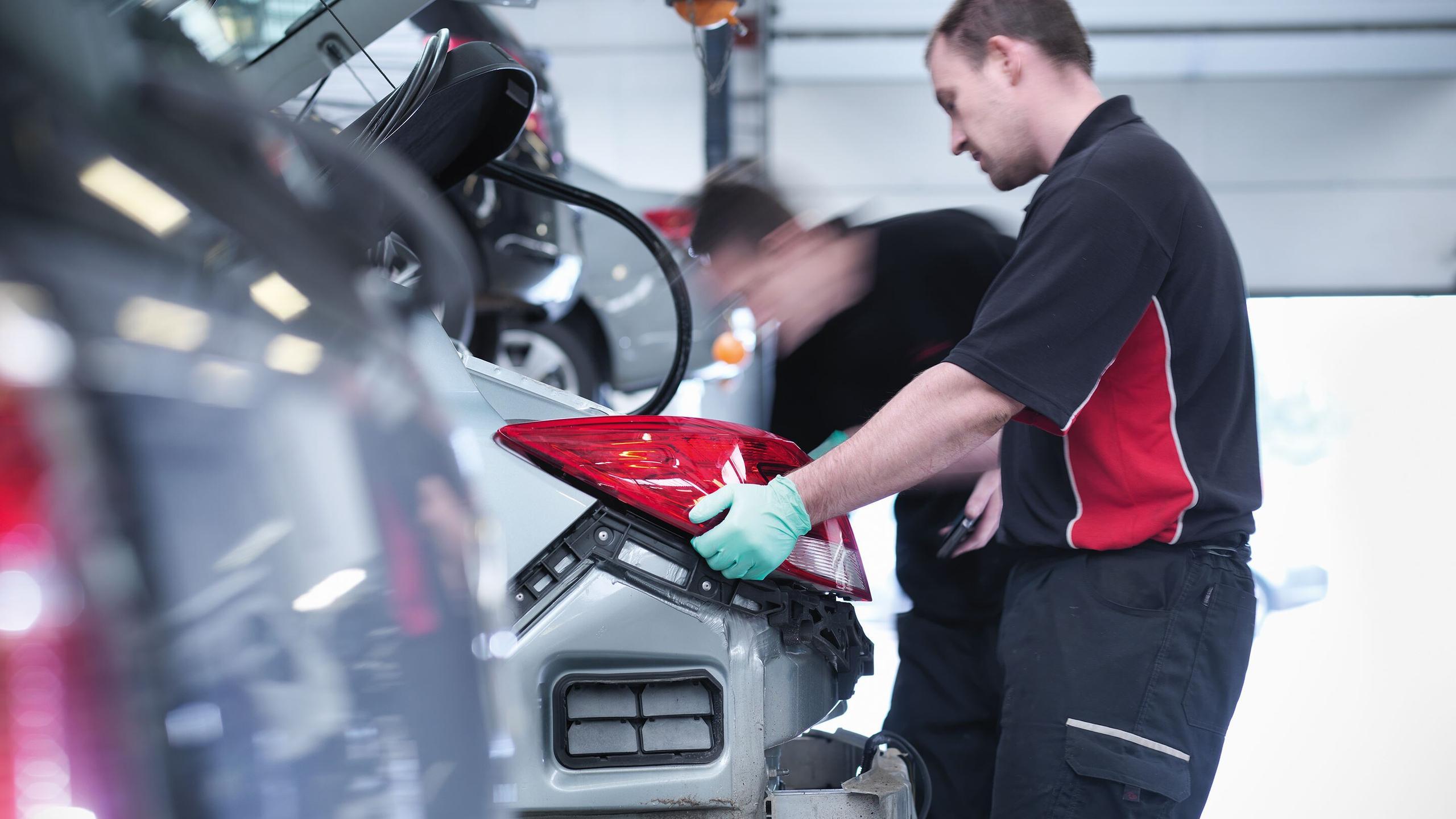 Male mechanic replacing rear tail light
