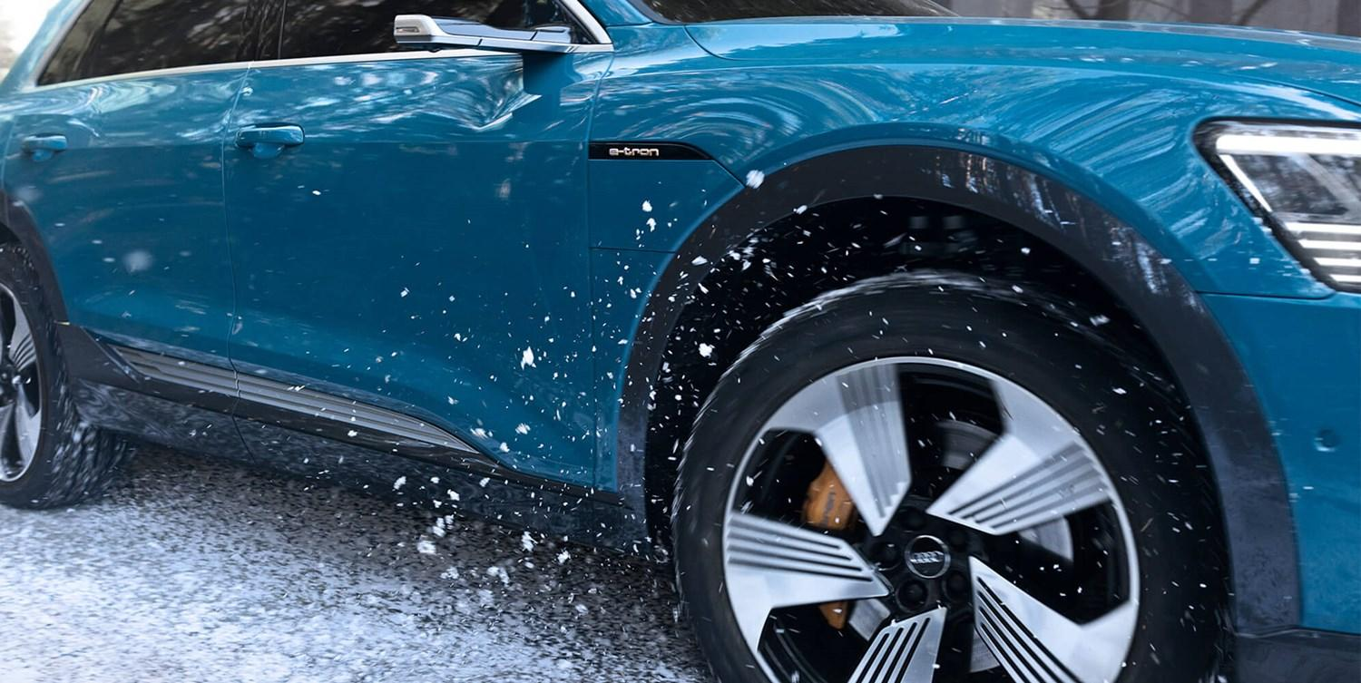 right hand side of a bright blue e-tron on snow, showing front wheel kicking up snow