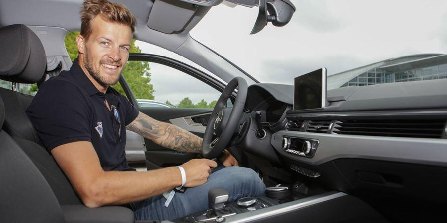 man with ligh brown short curly hair in a black polo shirt with tattoos on left arm sat in the driver seat of an automatic audi with the car door open