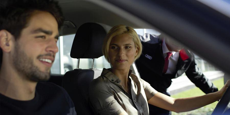 Man wirh short dark hair and stubble wearing a black t-shirt and a women with short blonde hair wearing a grey shirt sat in the driver seat, while a person in an audi uniforms opens the driver side door and looks into the car