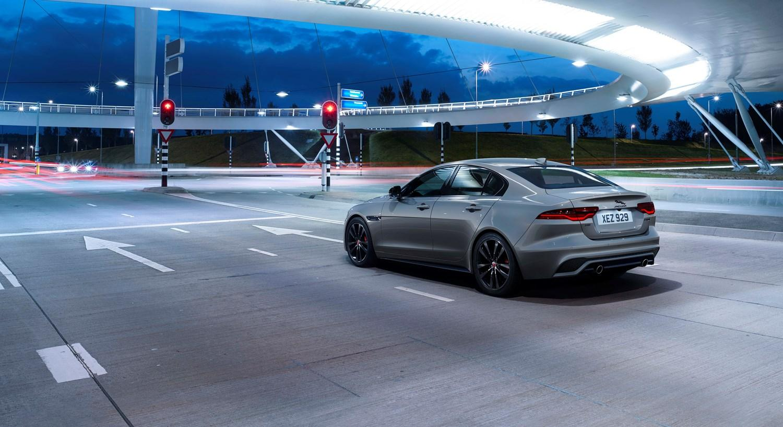 Grey Jaguar XE at a set of red traffic lights at night