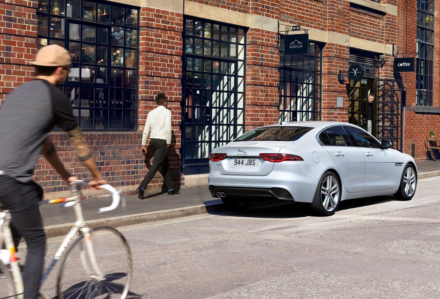White Jaguar XE packed alongside a kerb facing away. A man wearing a grey top, dark grey trousers and brown hat cycles a white bike along the road. The background is a brick building with multiple dark framed windows and a black shop sign. A man walks along the pavement