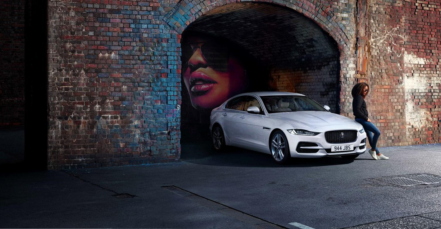 White Jaguar in a railway arch with an image of a lady set in the alcove of the arch. A lady is perched on the bonnet of the car