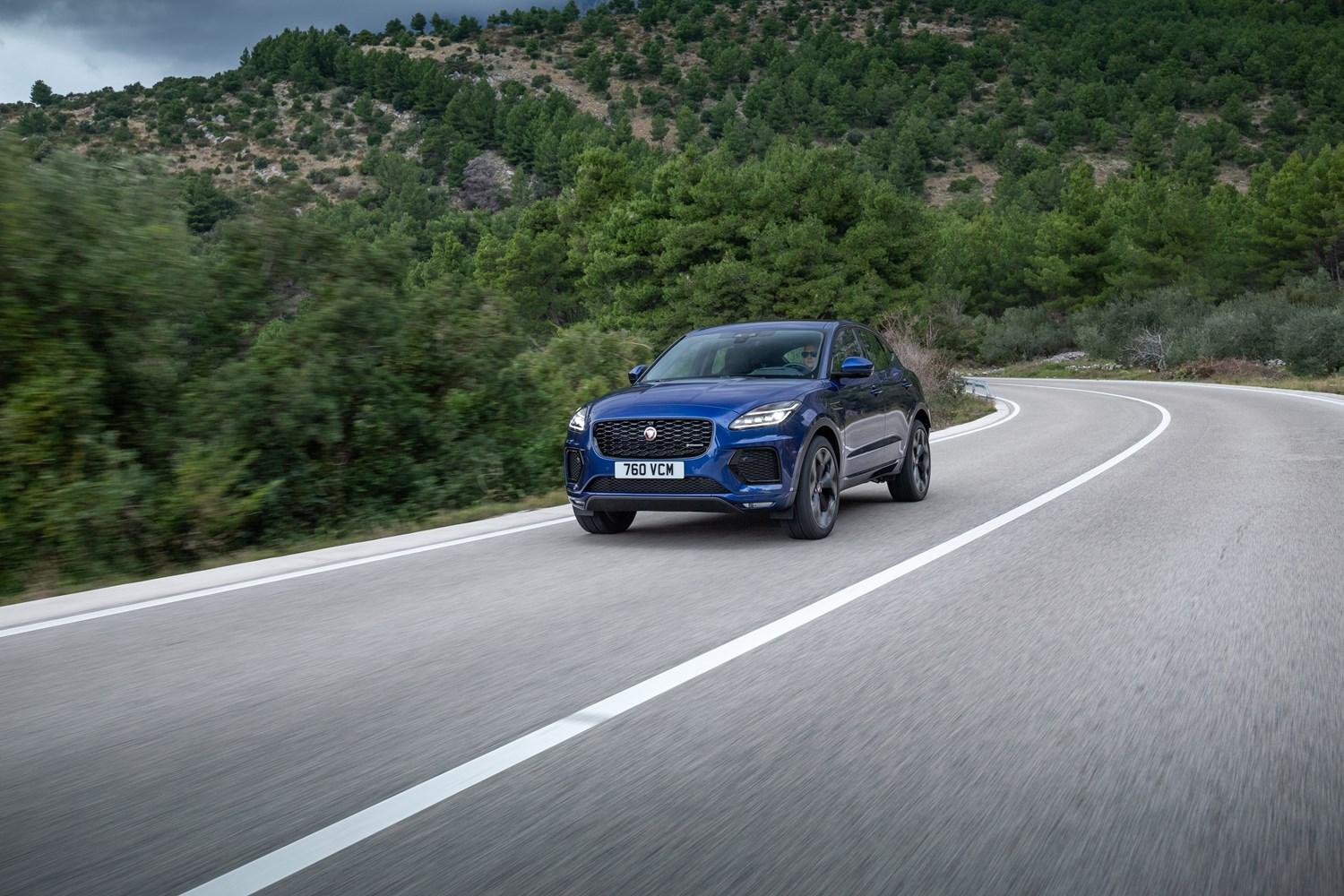 Bleu Jaguar E-PACE driving along a mountain road with green mountains in the background