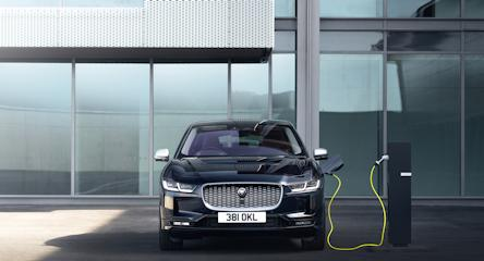 Black I-PACE plugged into charging point with yellow cable in front of a mostly glass building